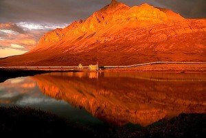 The Alaska oil pipeline reflected in a beautiful lake at sunset